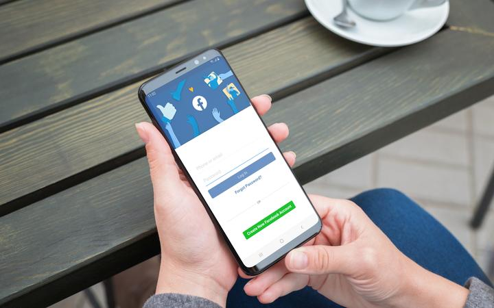 SARAJEVO, BOSNIA AND HERZEGOVINA - JULY 14, 2019: Woman use Samsung Galaxy smartphone to log in on the Facebook social network account.