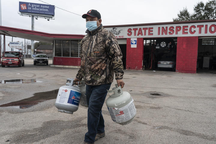 A man brings propane tanks to refill at a propane gas station after a winter freeze caused electricity blackouts in Houston, Texas, 18 February 2021