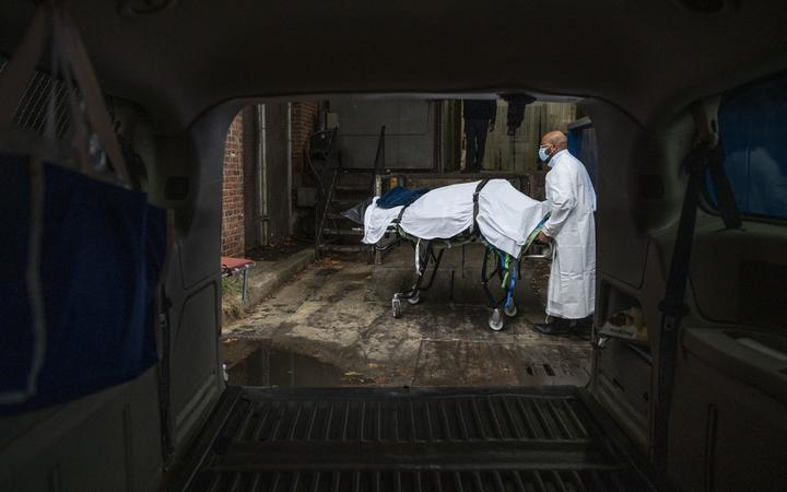 In this file photo taken on December 24, 2020 Maryland Cremation Services transporter Reggie Elliott brings the remains of a Covid-19 victim to his van from the hospital's morgue in Baltimore, Maryland during the Covid-19 pandemic.