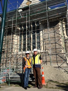 A photo of Pauline Scanlan and Andre Lovatt outside the scaffold-covered Arts Centre
