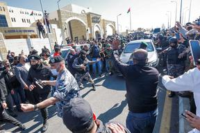 People stand on the side as Jordan's King Abdullah II arrives at al-Hussein New Salt Hospital in the town of Salt.