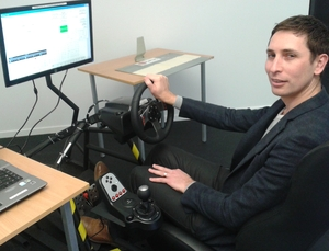 Behavioural scientist Jared Thomas seated at OPUS Research's audio tactile profile simulator, which is used to test how people detect rumble strips of different heights and spacings.