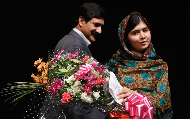 Malala Yousafzai, stands with her father Ziauddin Yousafzai, after addressing the media in Birmingham.