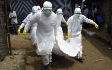 Red Cross workers carry the body of a person suspected of dying from Ebola in the Liberian capital Monrovia.