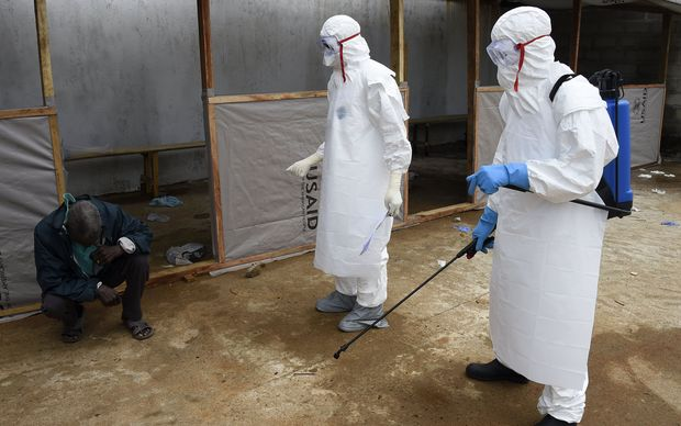 A man thought to be suffering from the Ebola virus waits to receive treatment from medical staff at Island hospital in the Liberian capital Monrovia.
