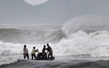 Indian fishermen negotiate their skiff through rough waves ahead of the landfall of Cyclone Hudhud.