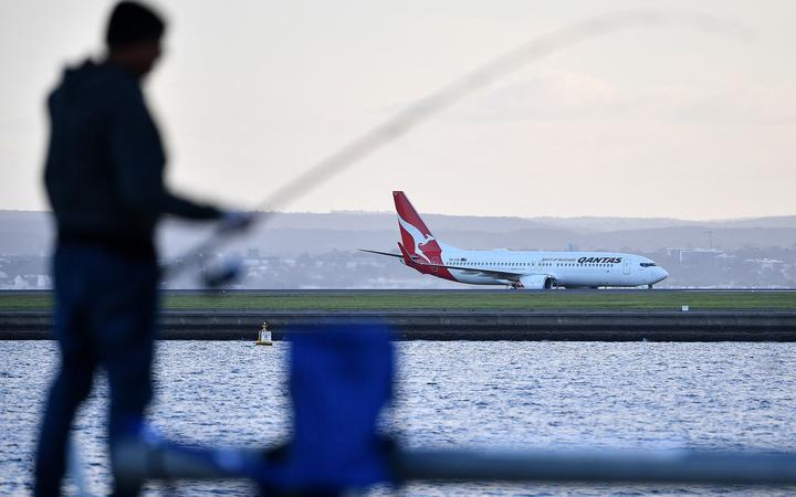 A Qantas Airline plane lands on Sydney International Airport in Sydney on March 27, 2020.