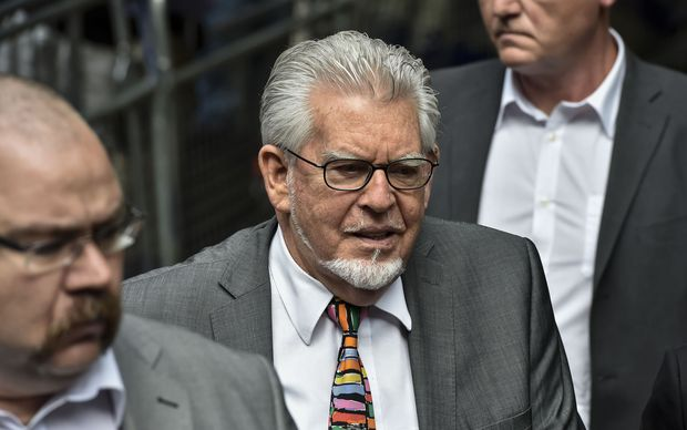 Rolf Harris (C) arrives at Southwark Crown Court in central London on 4 July 2014.