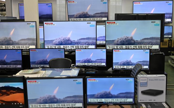 Television screens show file footage of North Korea's missile test as a news programme broadcasts reports about North Korea's suspected ballistic missile test, at an electronics mall in Seoul on March 25, 2021.