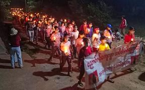 This handout photo taken and released by Dawei Watch on March 27, 2021 shows protesters holding candles as they take part in a demonstration against the military coup in a village near Dawei. (