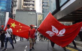 Members of a pro-Beijing and pro-police group hold large China national flag and Hong Kong SAR flag in Tsim Sha Tsui, Hong Kong, on September 18, 2019.