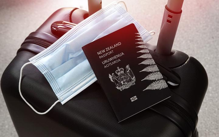 Travelling during covid-19 pandemic. New Zealand passport and protective mask on black suitcase