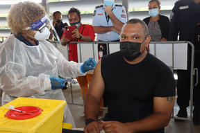 The Controller of the PNG National Pandemic Response, David Manning, receives a shot of the Covid-19 vaccine produced by Astrazeneca.