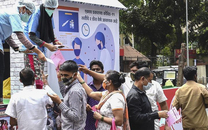 Workers of the Brihanmumbai Municipal Corporation (BMC) distribute face masks during an awareness campaign against the spread of the Covid-19 coronavirus, in Mumbai on April 8, 2021.