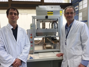 A photo of Ben Schon and Tim Woodfield in front of the 3D bioprinter