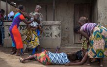 Women faint while volunteers take away the body of a woman who died of Ebola in Sierra Leone.