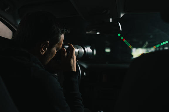A generic photo of a man in his car doing surveillance with a camera.