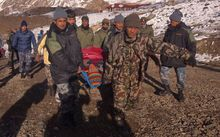 An injured survivor of the snowstorm in the Himalayas is rescued.