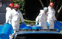 Hazmat workers prepare to decontaminate the apartment where a second nurse who tested positive for Ebola lives.