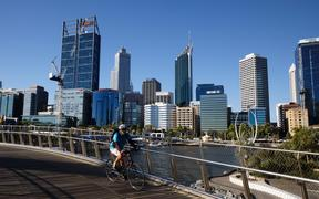 A cyclist rides along a deserted walkway in the normally busy Elizabeth Quay area in Perth on January 31, 2021,