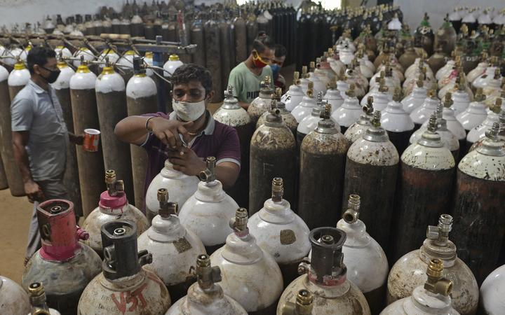 Workers arrange medical oxygen cylinders to be transported to hospitals amid Covid-19 coronavirus pandemic at a facility on the outskirts of Chennai on April 24, 2021.