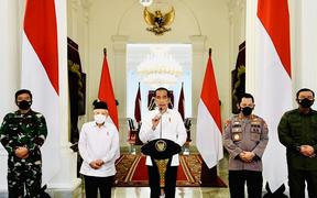 President Joko Widodo, flanked by his vice president and top military figures, announces the killing of the top intelligence official in Papua.