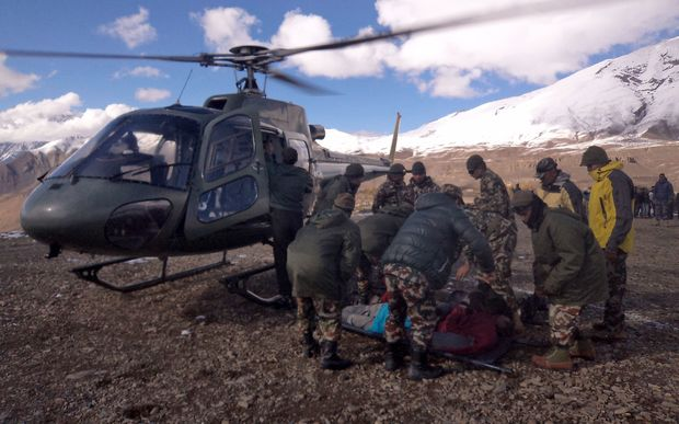An injured survivor is assisted by army personel into a Nepalese Army helicopter in Manang District, along the Annapurna Circuit Trek.