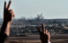 Kurdish onlookers react as they watch smoke billowing from Kobane, which has been under attack by Islamic State.