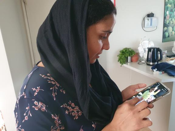 An photo of Gagandeep Kaur looking at an image of her daughter, Nimrat who is still in India.