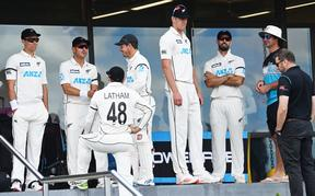 The Black Caps wait during a break in play at the Bay Oval.