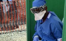 A health worker sits at MSF's Ebola treatment centre inside the Samuel K Doe stadium in Monrovia, Liberia.