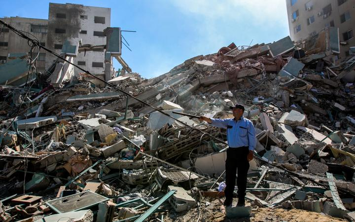 A Palestinian policeman stands in the rubble of a building destroyed by an Israeli airstrike that housed The Associated Press' offices in Gaza City, Palestine on 15 May 2021.