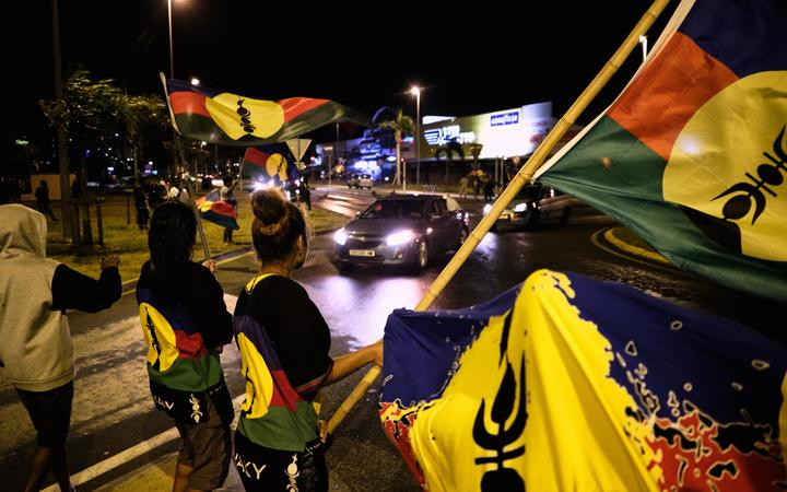 FLNKS supporters wave the Kanak flag of New Caledonia