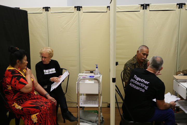 Malia Su-emalo Lui (left cubicle) and Seumanu Va'a Robertson (right) receive information about Covid-19 vaccination before receiving the jab at a public vaccination event arranged by the Catholic Church in Wellington, 9 June 2021.