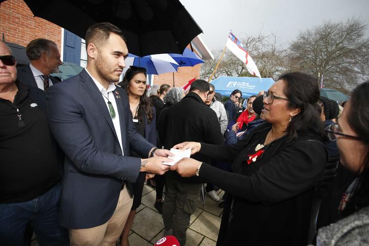 Far North councillor Moko Tepania (left) receives the Stop SNAs petition delivered by the hikoi, from Hinerangi Himiona.
