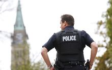 A police officer stands guard with the Peace Tower in the background following shootings in downtown Ottawa.