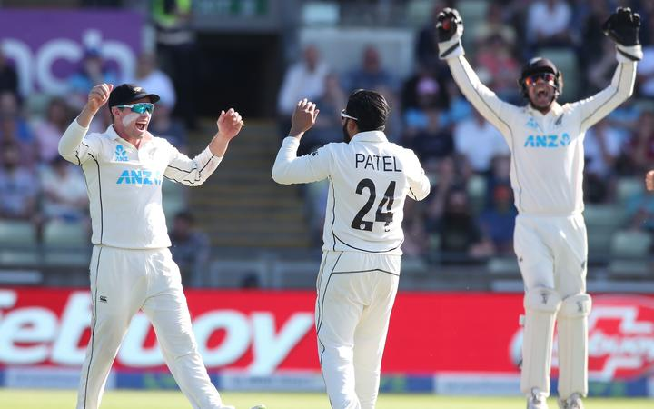 Ajaz Patel celebrates taking the wicket of Joe Root with Tom Latham (left) and wicketkeeper Tom Blundell.