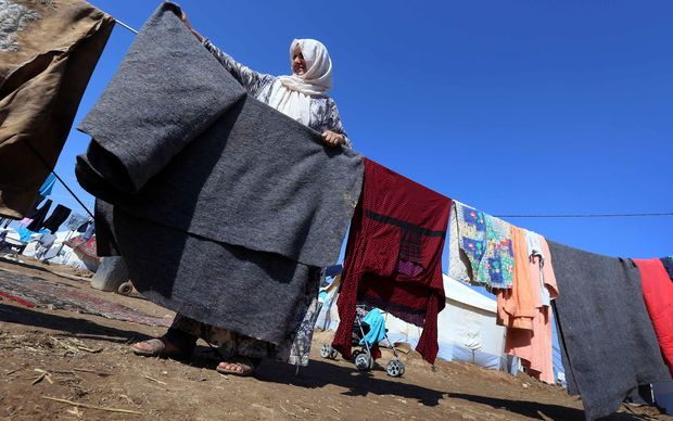 A displaced Iraqi woman, who fled her home due to attacks by IS, hangs up her washing at a refugee camp near Arbil.