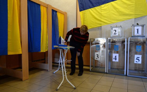 A member of a district electoral commission prepares booths at a polling station in Kiev.