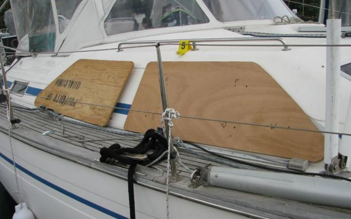Plywood storm coverings in position, but not secured over windows, on a Bavaria Oceans 47 sister ship.