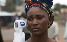 A health worker checks a woman entering Mali from Guinea for signs of Ebola.