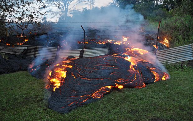 Red-hot lava from a slow-erupting volcano has reached a home on Hawaii's Big Island and is threatening an entire town.