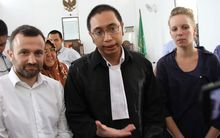 Two detained French journalists Thomas Dandois (L) and Valentine Bourrat (R) listen to their lawyer after their trial in Jayapura.