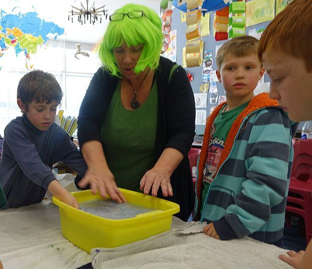 Teacher in bright green wig makes paper with a group of primary school students