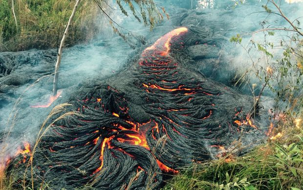 This image provided by the US Geological Survey (USGS) shows a breakout of ropey pāhoehoe lava from the volcano in Pahoa, Hawaii, upslope of Apaʻa Street burning vegetation near the Pāhoa transfer station.