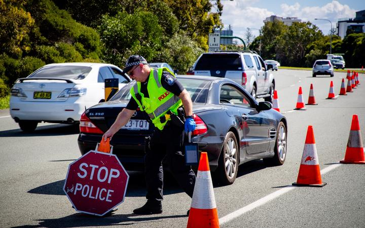 A Queensland police officer moves a stop sign at a vehicle checkpoint on the Pacific Highway on the Queensland - New South Wales border, in Brisbane on April 15, 2020.