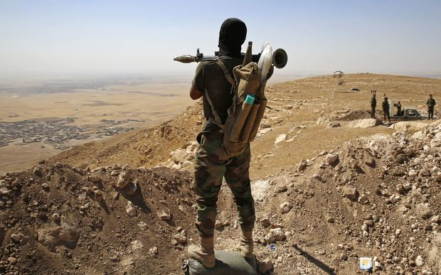 A Kurdish Peshmerga fighter overlooking a village near Mosul controlled by Islamic State.