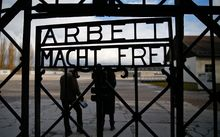 Visitors walk past the main gate at the Dachau concentration camp.