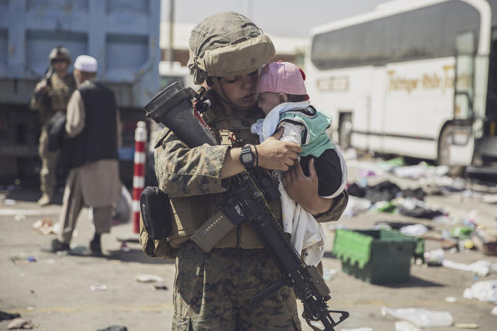 This U.S. Marine photo released on August 29, 2021, shows a U.S. Marine carrying a baby with the 24th Marine Expeditionary Unit (MEU) as the family arrives at the Hamid Khan Karzai International Airport, Kabul, Afghanistan. Proceeding with the family through the Evacuation Control Center (ECC) during the evacuation.  On August 28, 2021.