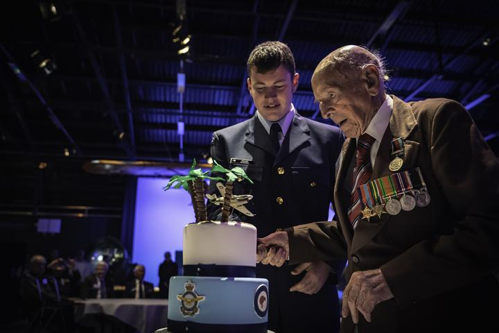 Ron Harmans was cutting his 108th birthday cake with the help of the youngest ever airman in the RNZAF, Aircraft Hamish Batchiller (then 18).